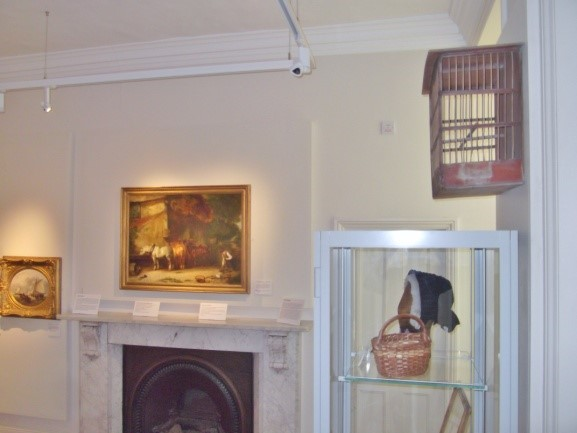 A birdcage overlooks its corresponding painting
